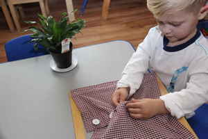 child learning to button shirt at montessori school - plano, tx