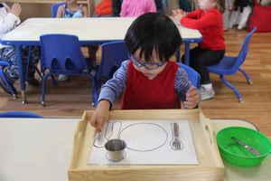 toddler setting the table at Kidz Camp Montessori School - Plano, TX
