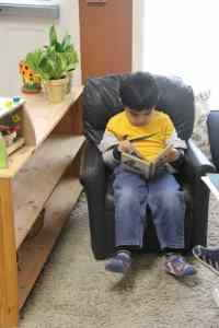 Young elementary boy reading independently at Kidz Camp Montessori School - Plano, TX
