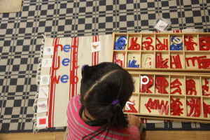 girl working on spelling words at Kidz Camp Montessori school - Plano, TX