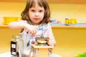 girl grinding coffee at kidz camp montessori - plano, tx